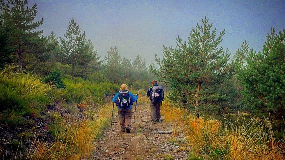Una pareja de peregrinos emprende el descenso hacia el embalse de Salime.