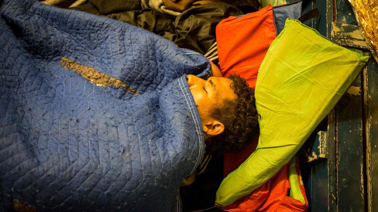 Un migrante duerme en el piso a bordo del barco de rescate con bandera holandesa «Sea Watch 3» que navega por la costa de Malta