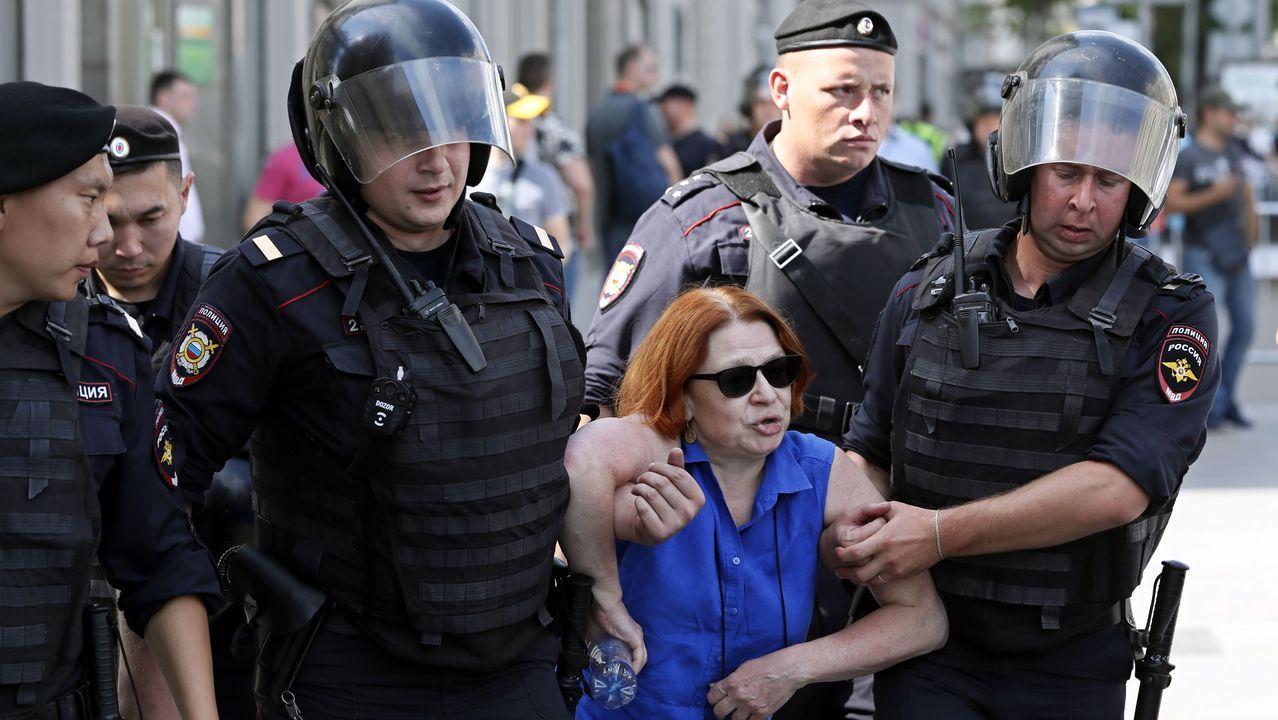 Agentes de la policía rusa conducen a una de las mujeres detenidas en el centro de Moscú