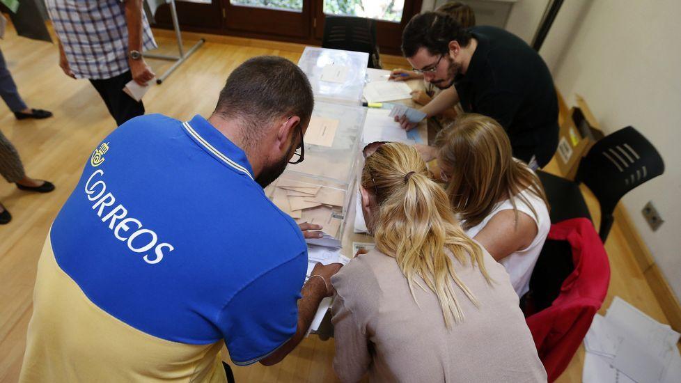 Un funcionario de correos entrega en una de las mesas del Centro Cultural Volturno, en la localidad madrileña de Pozuelo de Alarcón, los votos por correo destinados a este colegio electoral