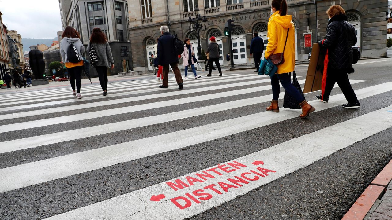 Varias personas cruzan un pase de peatones con un aviso de recomendación de distanciamiento social pintado por el Ayuntamiento de Oviedo como forma de frenar la pandemia del coronavirus.