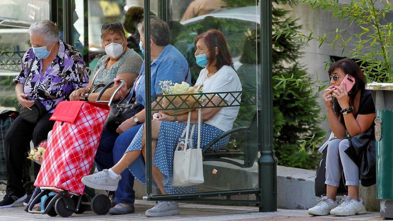 Adiós a los teléfonos 902.Una mujer fuma junto a la parada de un autobú, en el centro de Oviedo, mientras en la marquesina un grupo de ususarias se protege con mascarillas.