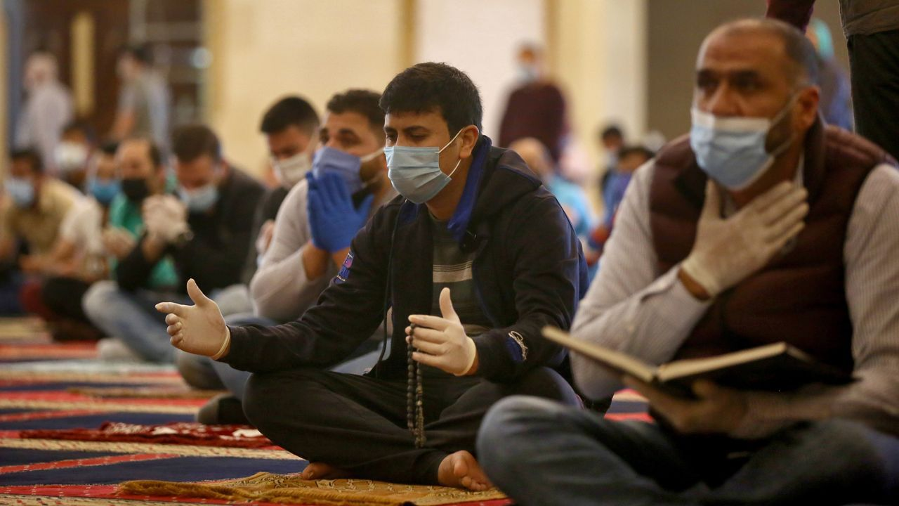 Los fieles mantienen la distancia social dentro mientras asisten a la oración en Beirut