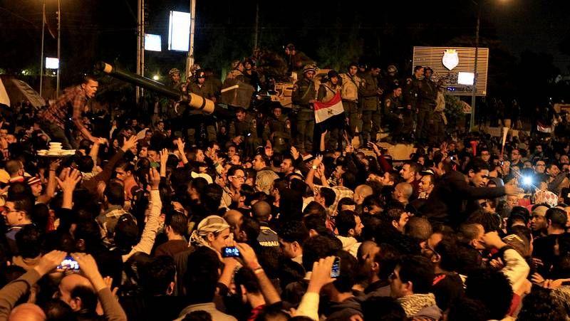 Un egipcio agita una bandera delante del palacio presidencial, protegido por policías en El Cairo.