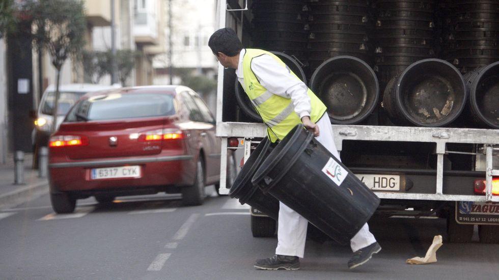 Un trabajador de la empresa de limpieza, durante el reparto de cubos en la calle Roberto Baamonde