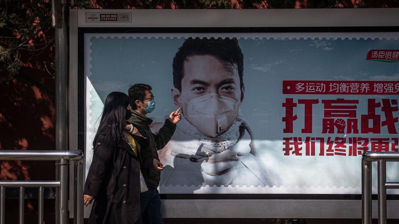 Un anuncio muestra a un hombre con mascarilla, en una calle de Pekín, China
