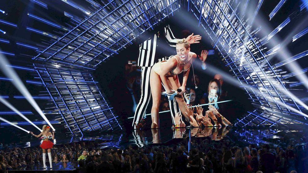 Miley Cyrus habla en el escenario con una imagen suya de fondo