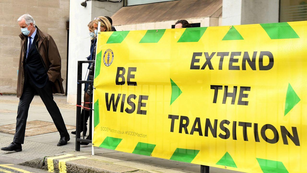El negociador europeo, Michel Barnier, pasa al lado de una pancarta con el lema dirigido a Johnson «Se sabio, extiende la transición»
