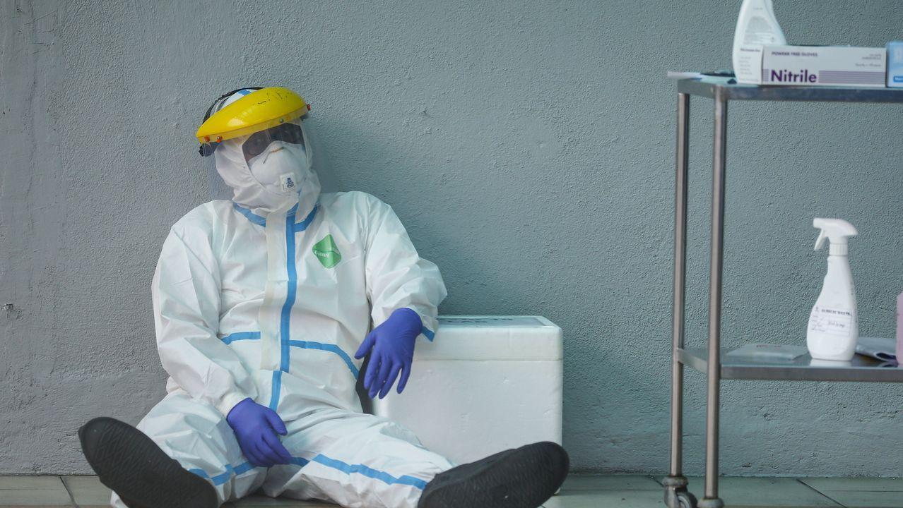 Un trabajador sanitario se toma un respiro ataviado con un traje de protección en Kuala Lumpur