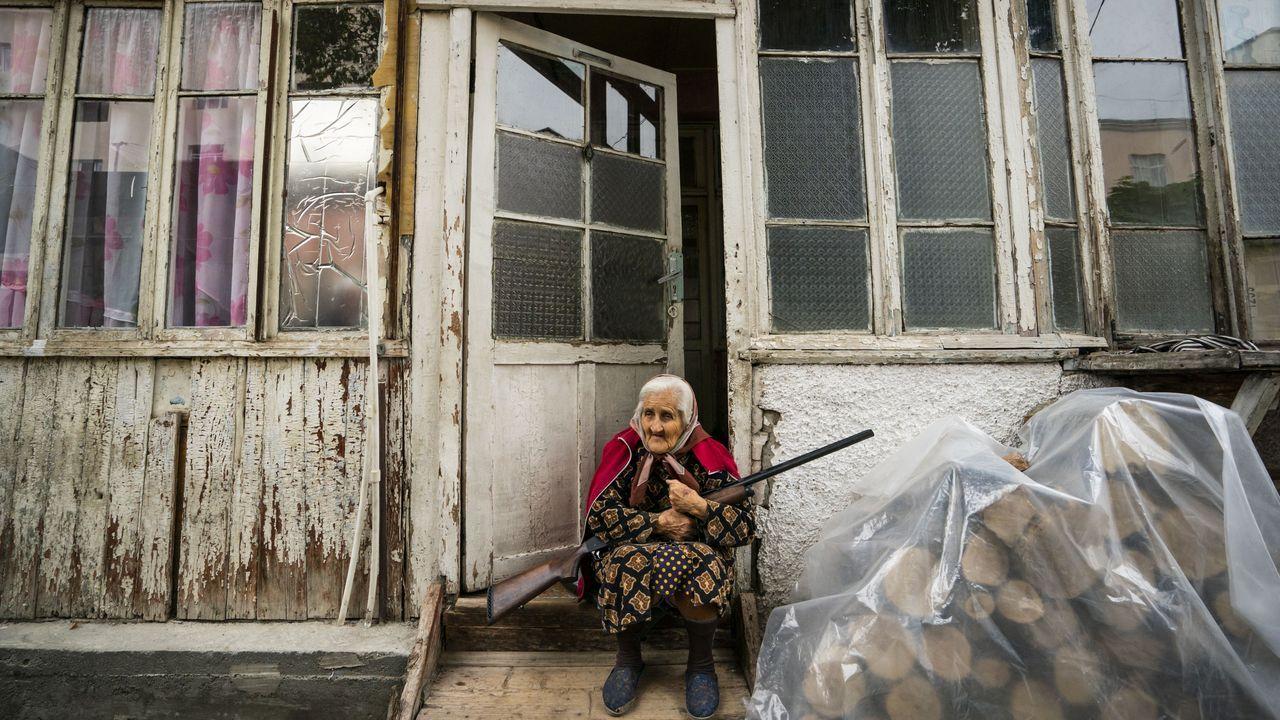 Una mujer sostiene una escopeta en la entrada de su vivienda, en la capital de Nagorno Karabaj