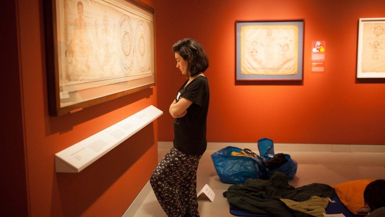 Una persona en pijama observando una de las obras que se exponen en el Rubin Museum, de Nueva York