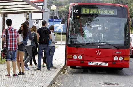 Estudiantes universitarios en una de las paradas del bus que viaja a los campus.