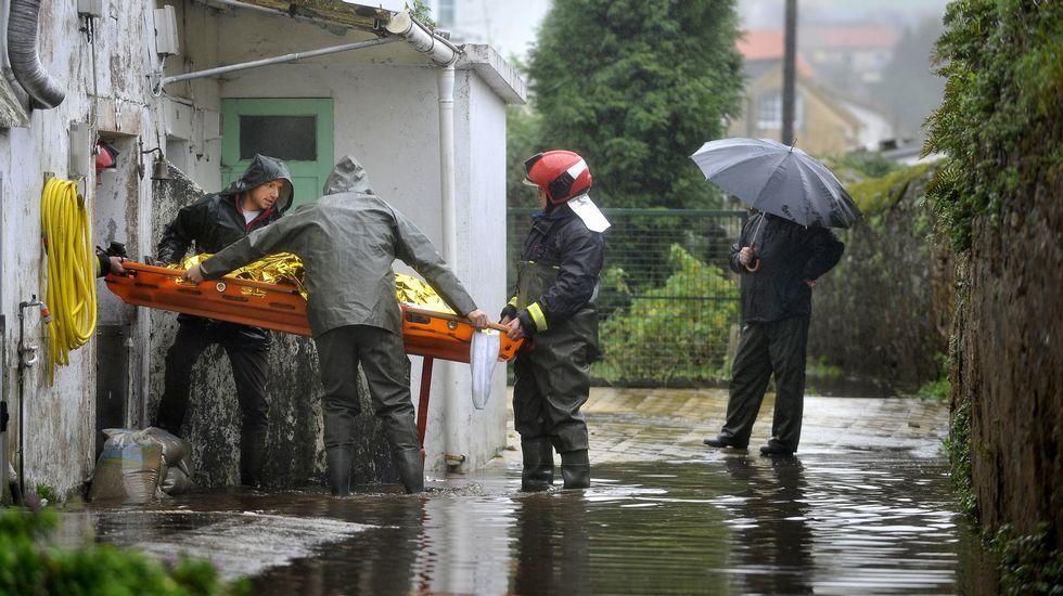 Evacuación de una persona en camilla en Neda.