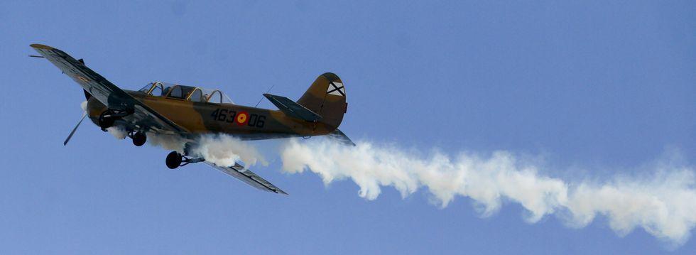 Un avión acrobático del ejército volando sobre Rozas ayer y soltando una estela de humo para que el público lo siguiese.
