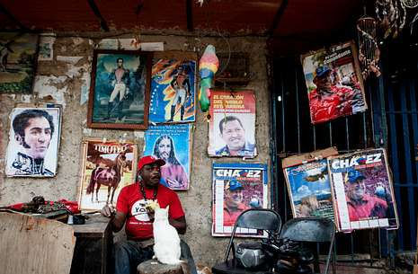Un hombre muestra su apoyo a Chávez con carteles en la entrada de su casa en Caracas.