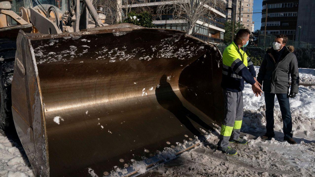 Operarios de limpieza trabajan limpiando la nieve en una calle de Madrid