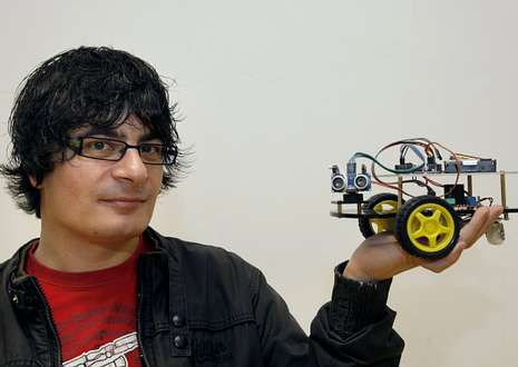 O informático, cun dos robots que pode verse na exposición que hai no auditorio.