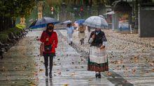 Dos mujeres pasen bajo la lluvia en el paseo de Los Álamos, en el centro de Oviedo