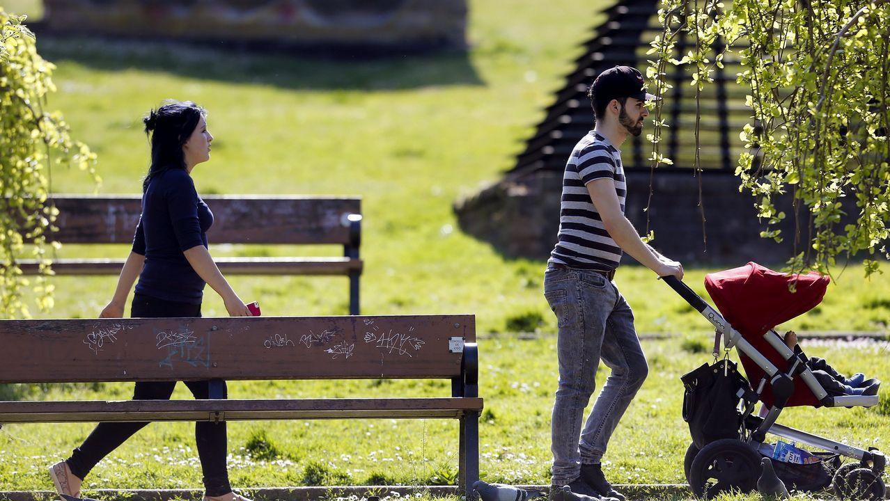 Una joven pareja paseando con su bebé por un parque de Vigo