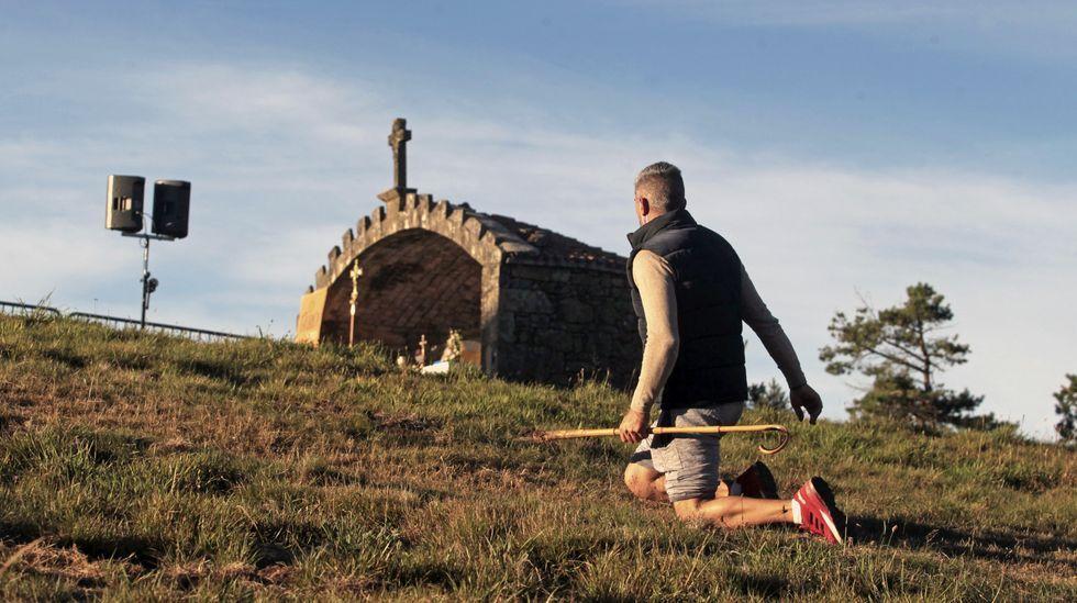 Las fotos de la romería 2002 en el Monte Faro.El cura Xabier Diéguez levanta una mascarilla ante los fieles que acudieron el 15 de agoto a la fiesta del monte Faro
