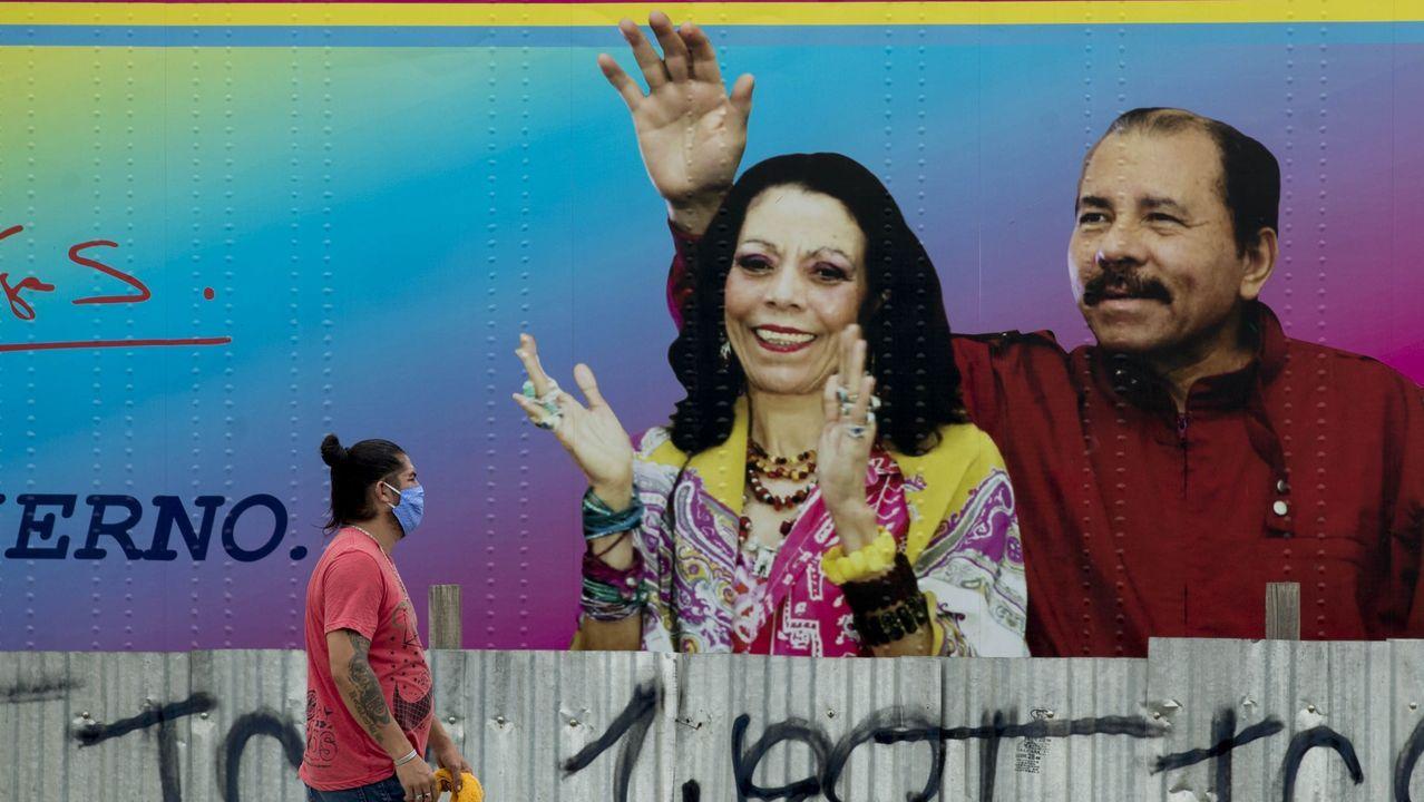 Un hombre pasa frente a un cartel del presidente Daniel Ortega y su esposa Rosario Murillo