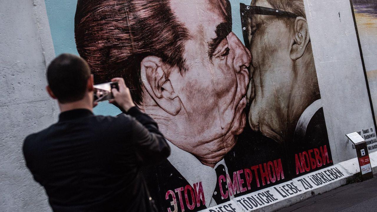 Un visitante fotografía un grafiti en la East Side Gallery de Berlín