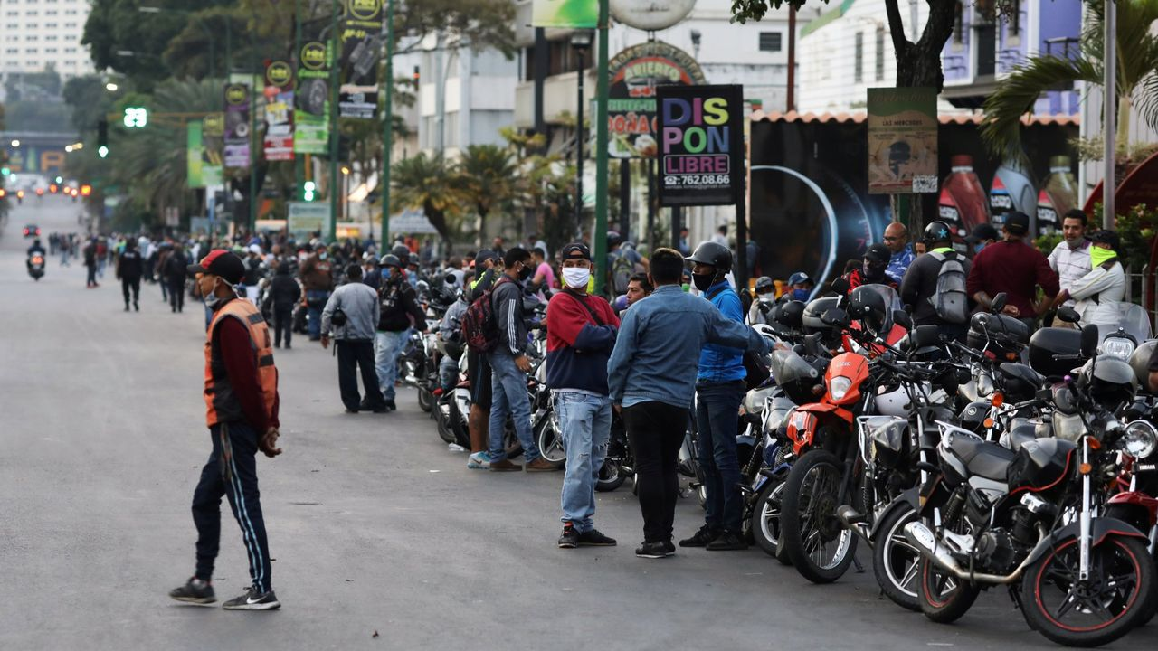 Motoristas hacen cola mientras esperan la apertura de una gasolinera en Caracas