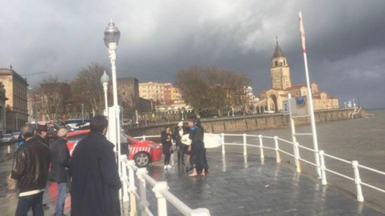 Varios agentes de la Policía Local de Gijón, junto al surfista rescatado