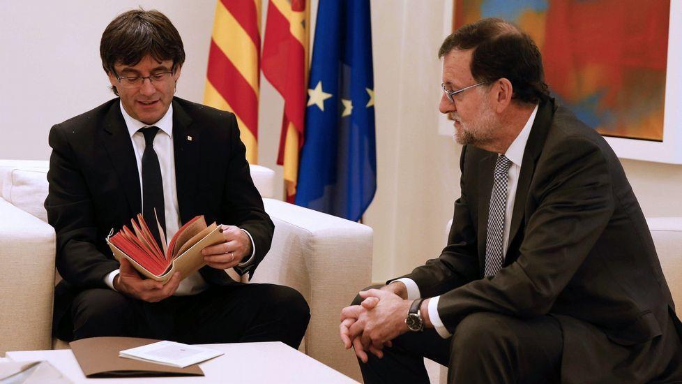 El presidente de la Generalitat, Carles Puigdemont (i), sostiene el facsímil de la primera edición de la segunda parte de «El Quijote» que le ha regalado el presidente del Gobierno en funciones, Mariano Rajoy, durante su primera reunión en el Palacio de la Moncloa, en Madrid, en la que ambos ratificaron sus argumentos ante las aspiraciones independentistas en Cataluña.