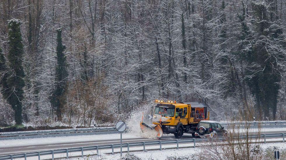 La Guardia Civil busca a un operario sepultado por un alud de nieve.Una máquina quitanieves limpia la carretera a la altura de Aller
