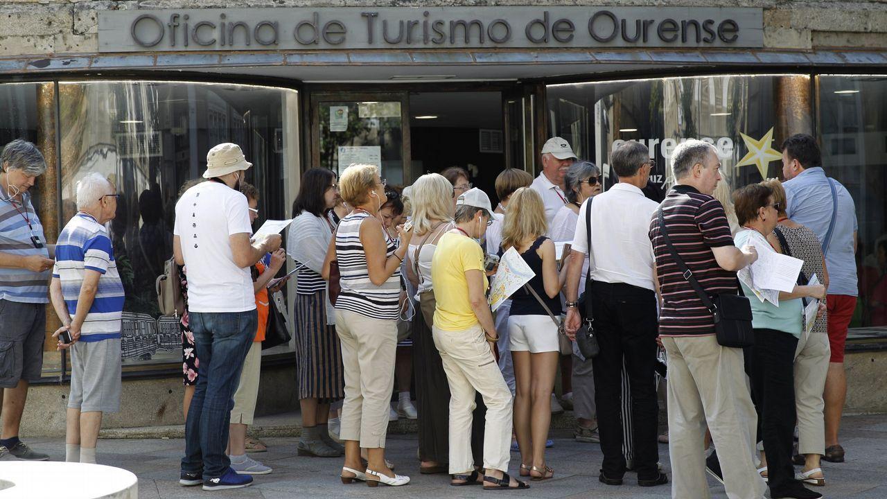 La moda ovetense, con estilo propio.Compradores miran un escaparate con rebajas en el centro de Oviedo