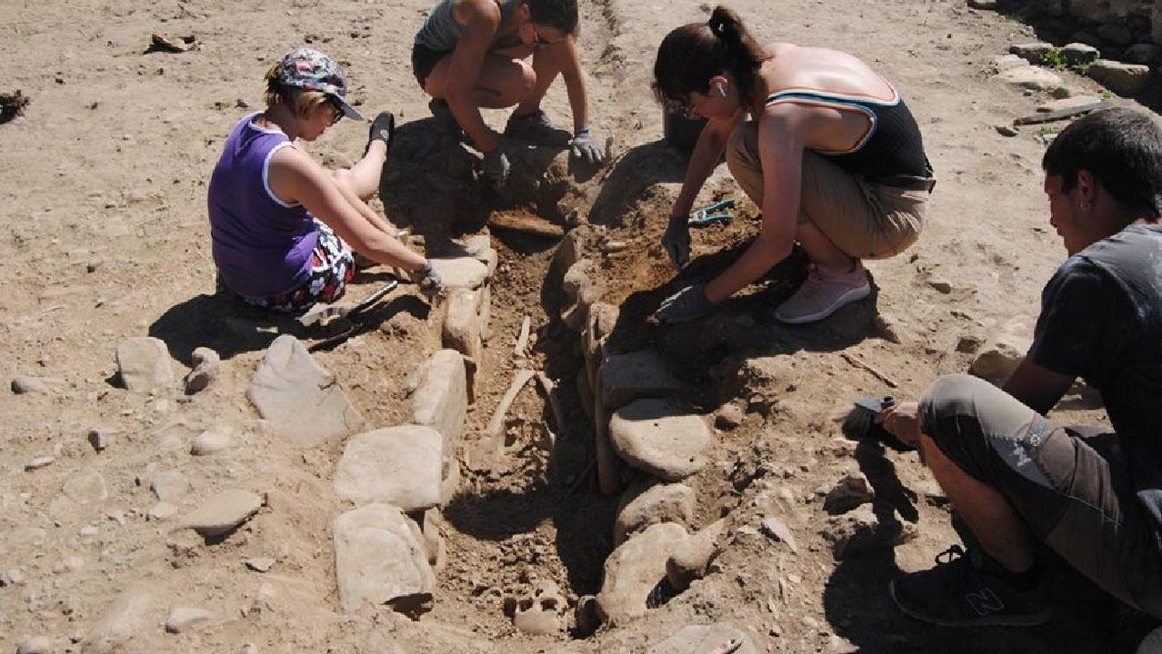 Un grupo de voluntarios excavan una de las antiguas tumbas descubiertas en el castro el año pasado