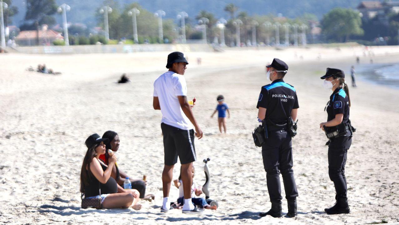 La policía local habla en la playa de Samil con un grupo de personas que estaban descansando en el arenal