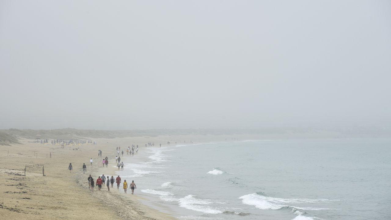 Mar  rojo  en Laxe: los efectos de una alga, en imágenes.Socorristas en la playa de A Frouxeira, en Valdoviño, este mes de julio