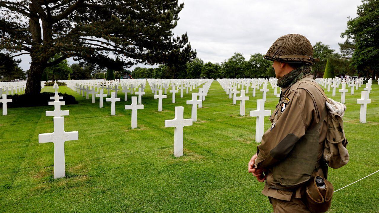 Un hombre que luce un uniforme militar estadounidense de época observa las tumbas en el cementerio galo de los soldados caídos estadounidenses en Colleville-Sur-Mer