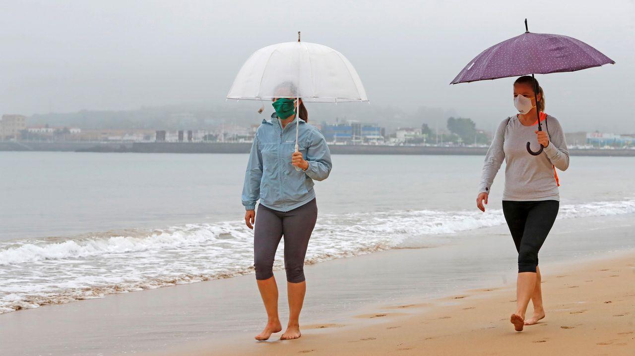 Unas personas pasean por la playa de Ssan Lorenzo de Gijon, durante la franja horaria permitida, hoy quincuagésimo sexto día del estado de alarma