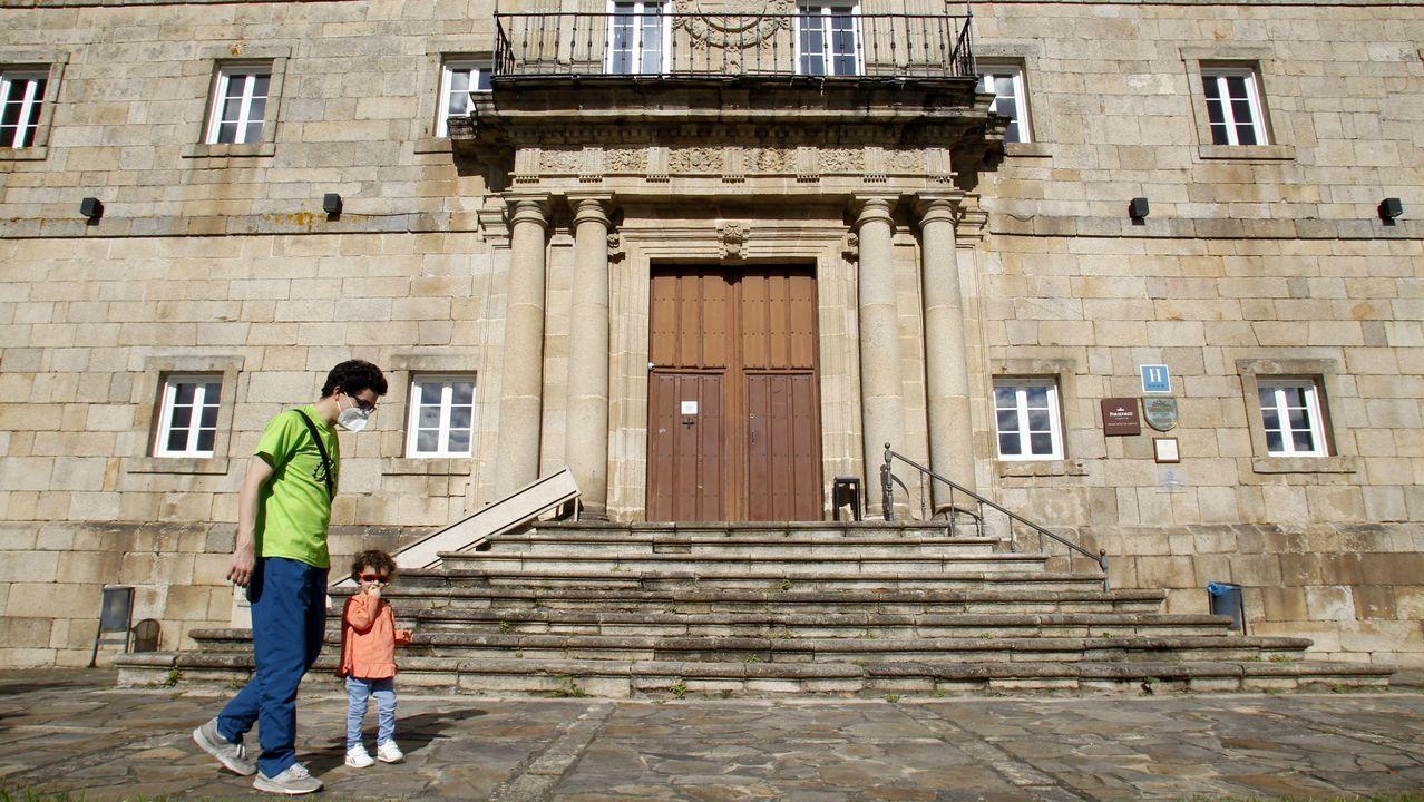 Las fotos del aguacero en Monforte.Un hombre pasea con una niña a mediados de mayo frente a la puerta cerrada del parador de turismo de Monforte