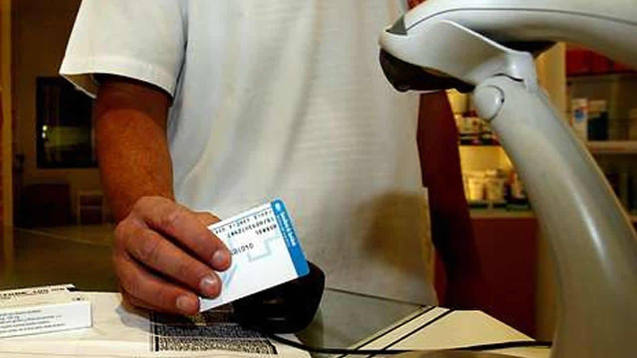 Un farmacéutico tramita la receta de un paciente con una tarjeta del Sergas