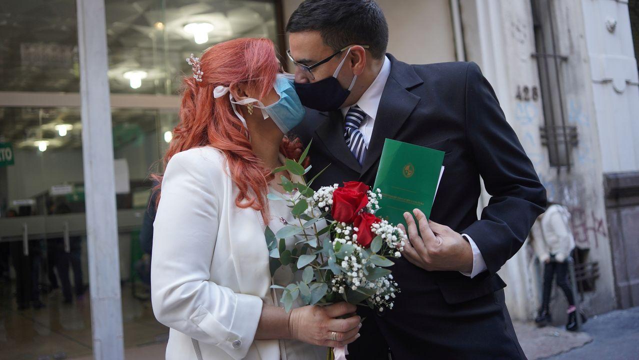 Laura Gómez y Martin Larzabal se besan mientras usan máscaras faciales después de casarse en Montevideo