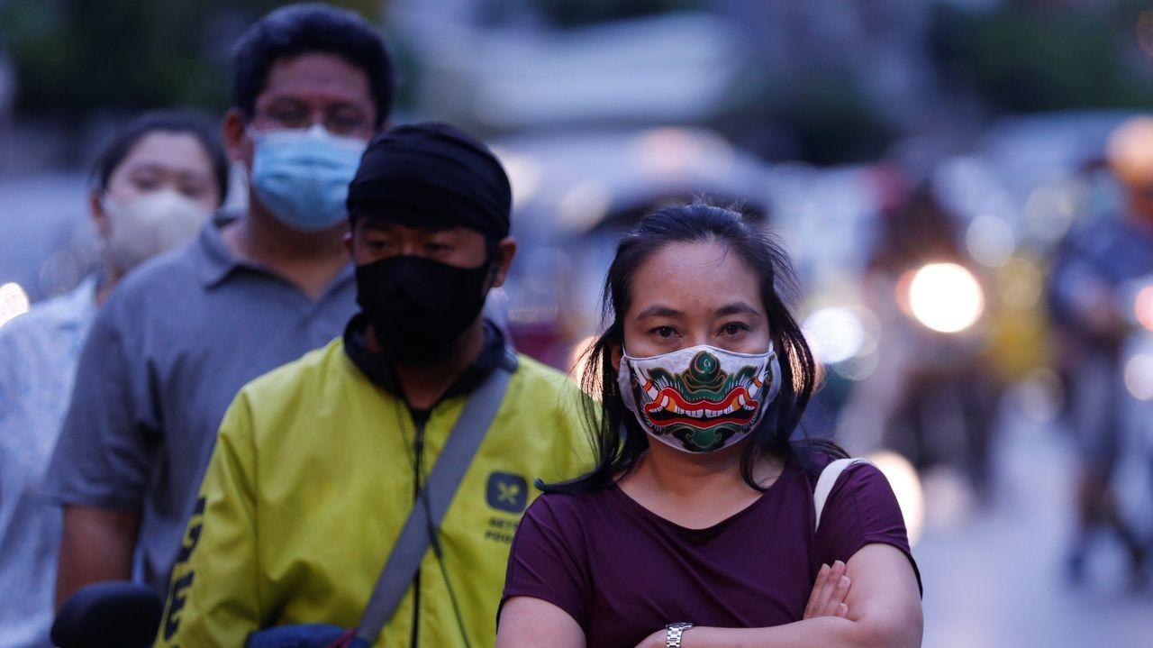 Ciudadanos hacen cola mientras esperan para coger alimentos en un puesto callejero durante en Bangkok