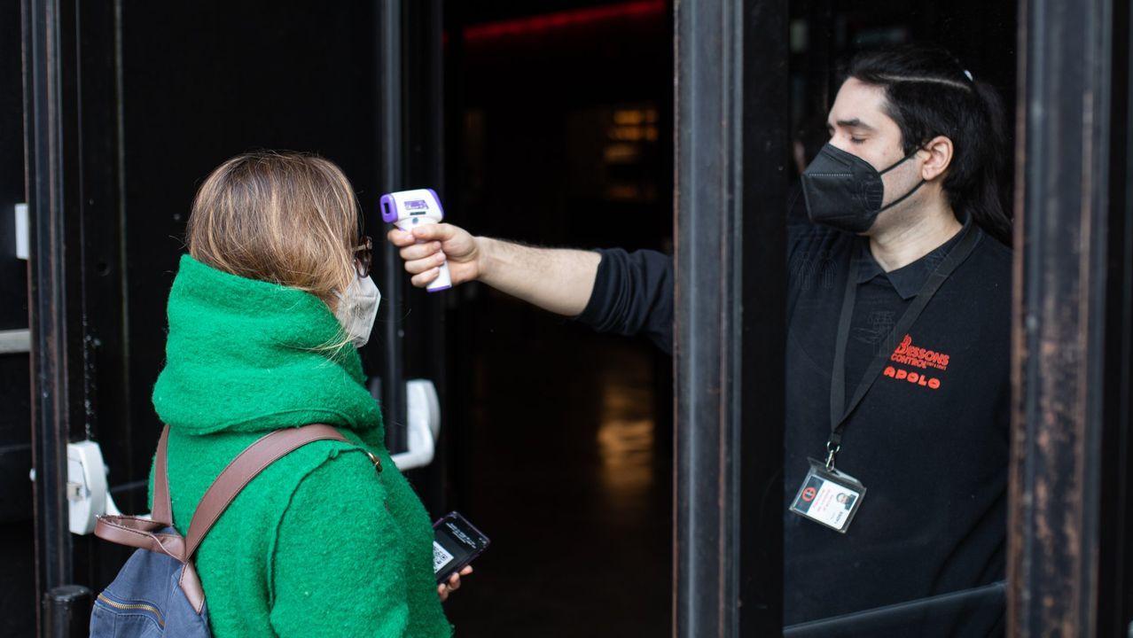Un trabajador de la sala Apolo, de Barcelona, toma la temperatura a una mujer antes de realizarse un test de antígenos rápido para poder acudir al concierto masivo de Love of Lesbian el 27 de febrero