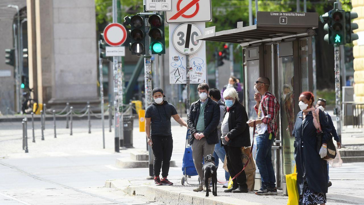 Personas con mascarillas esperan en una parada de autobús en Milán, Italia.