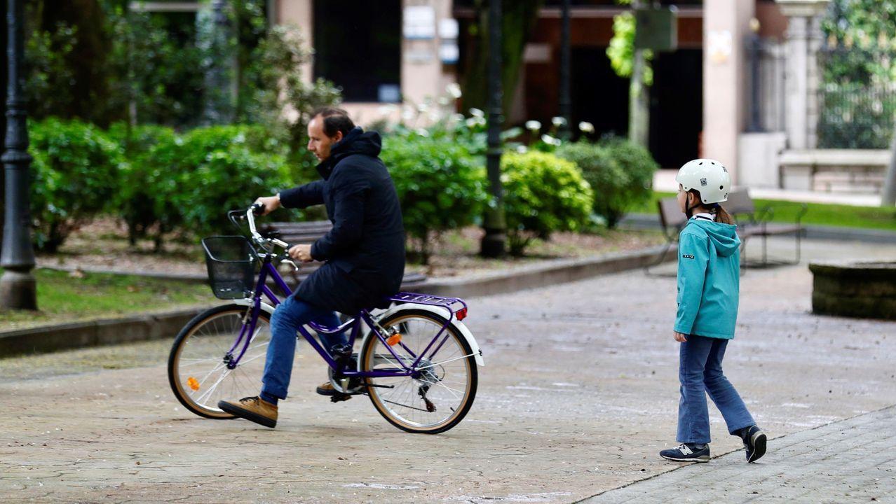Un padre pasea con su hija este lunes en Oviedo,