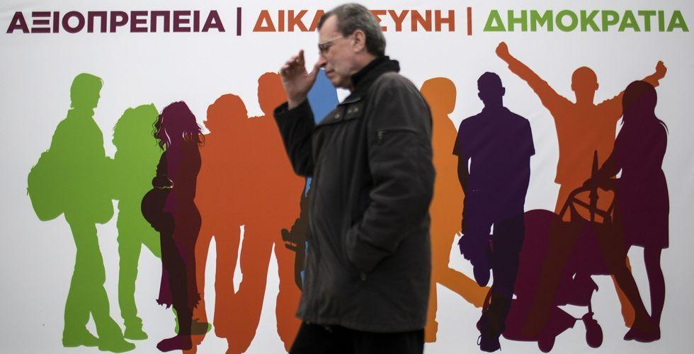La jornada electoral en Grecia.Un hombre camina en Atenas ante un cartel electoral de Syriza, formación a la que los sondeos atribuyen la victoria.