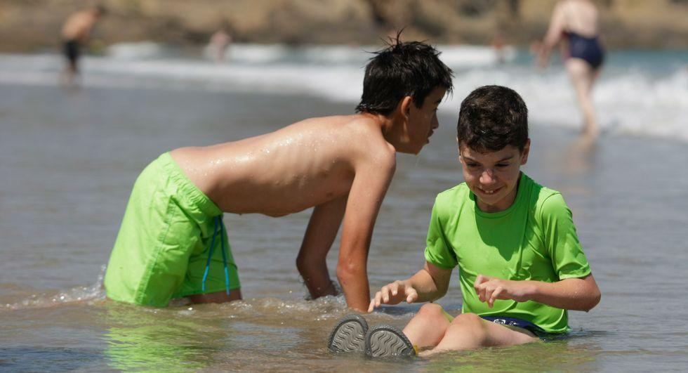 Dos niños juegan en la orilla durante la actividad en Bastiagueiro.