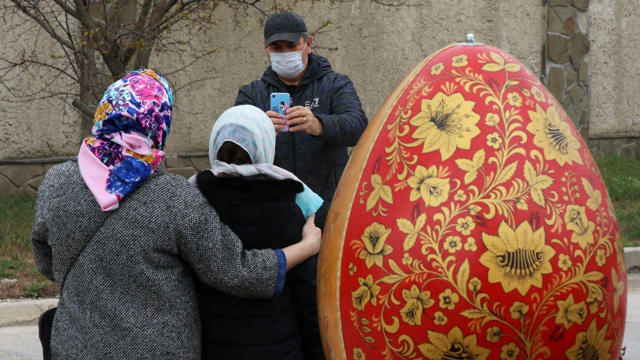 Un hombre le saca una foto a una mujer después de una ceremonia para bendecir los pasteles y los huevos de Pascua en la víspera de la Pascua ortodoxa, en Yevpatoriya, Crimea