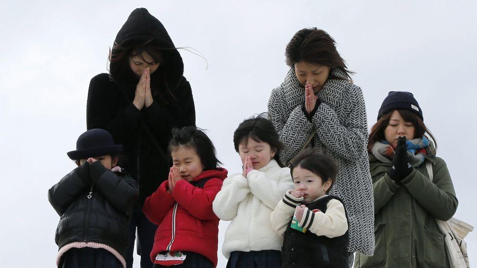 Varias personas guardan un minuto de silencio en memoria de las víctimas.