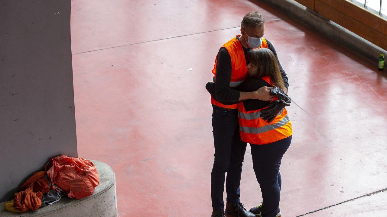 En Ginebra, dos voluntarios se reconfortan tras participar en un reparto de productos de primera necesidad entre gente sin recursos