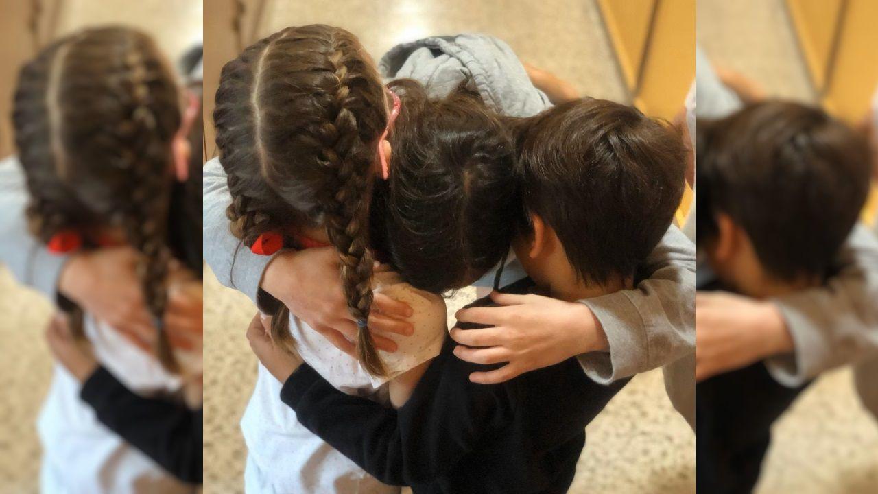 Tres hermanos del centro coruñés San José de Calasanz liberan en un abrazo sus emociones después de haber recibido la visita de un familiar. De momento, padres e hijos pueden verse, pero no besarse ni tocarse
