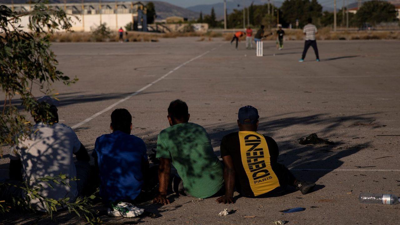 Un grupo de refugiados se entretiene jugando al criquet en una zona industrial de Atenas
